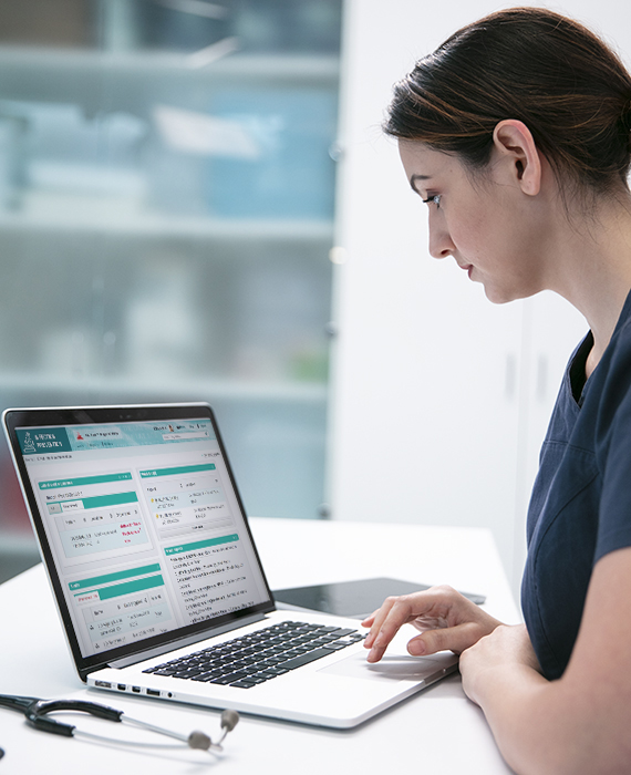 Female nurse using ICNET software on laptop in healthcare clinic